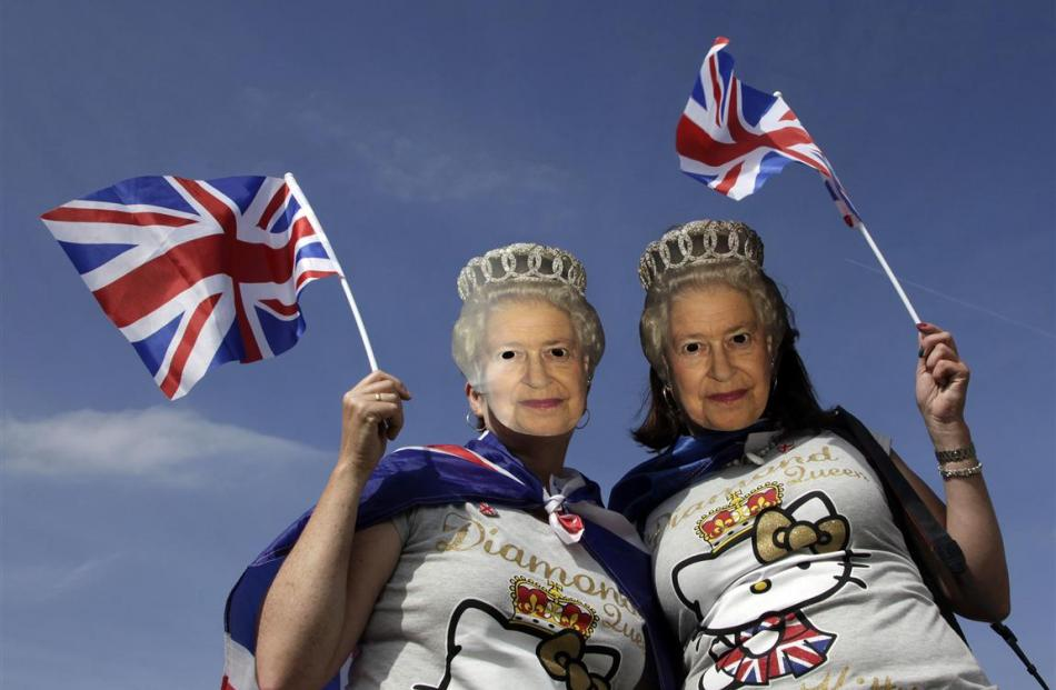 Two women, wearing masks depicting Britain's Queen Elizabeth, pose for a picture during a Jubilee...