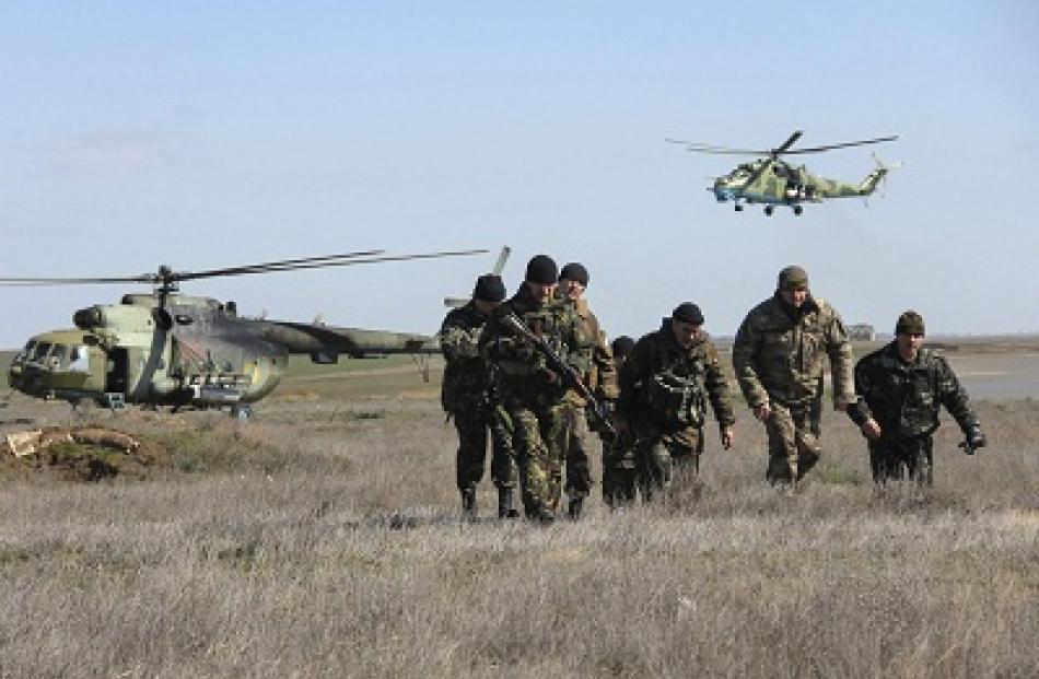 Ukrainian soldiers and military helicopters are seen near the village of Salkovo, in Kherson...