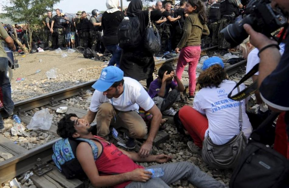 UN workers help a man who collapsed at the border dividing Macedonia and Greece. REUTERS/Ognen...
