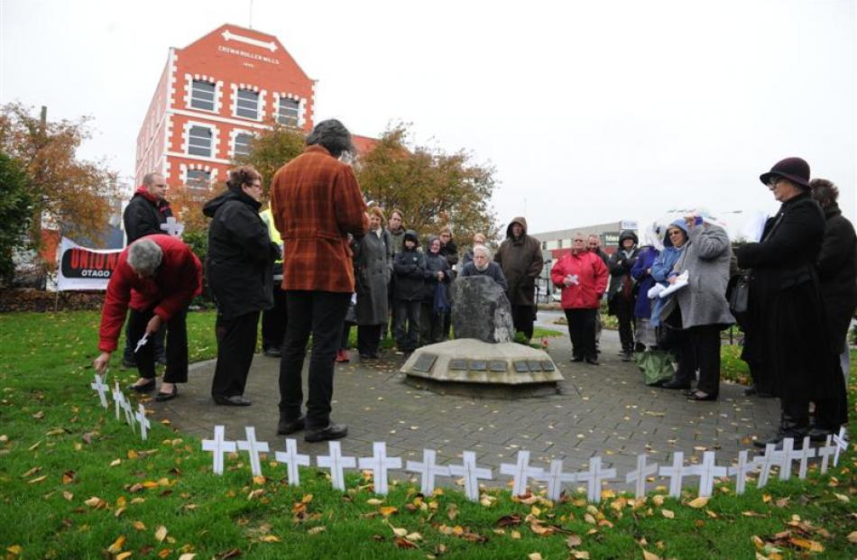 Unions Otago secretary Malcolm Deans (front left) reads a list of people who have died recently...