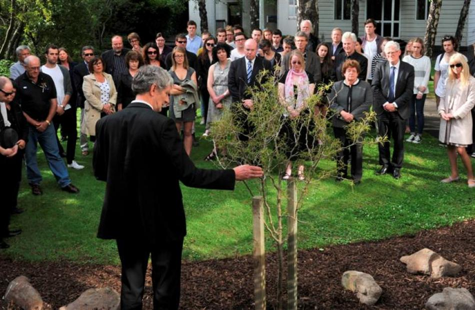 University of Otago chaplain the Rev Greg Hughson says a prayer beside a kowhai tree planted in...