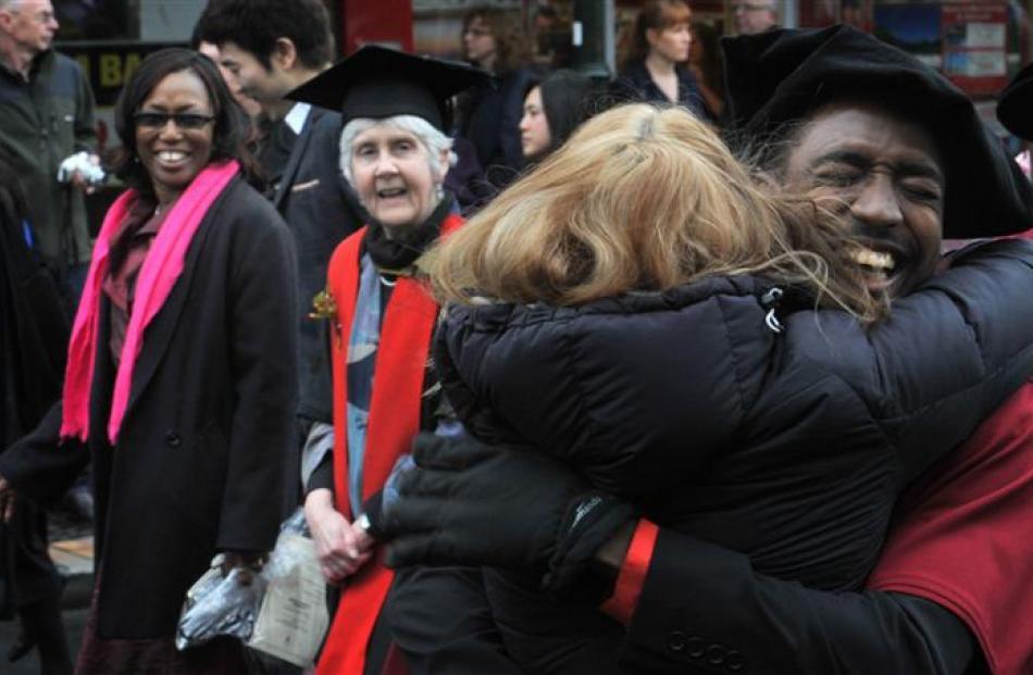 University of Otago PhD graduate Keron Niles receives a  hug during a graduation procession in...