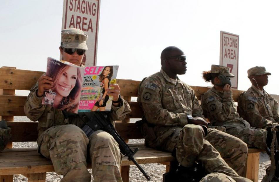 US Army soldier SSG Norma Gonzales of 426 Civil Affairs Battalion reads a magazine while waiting...