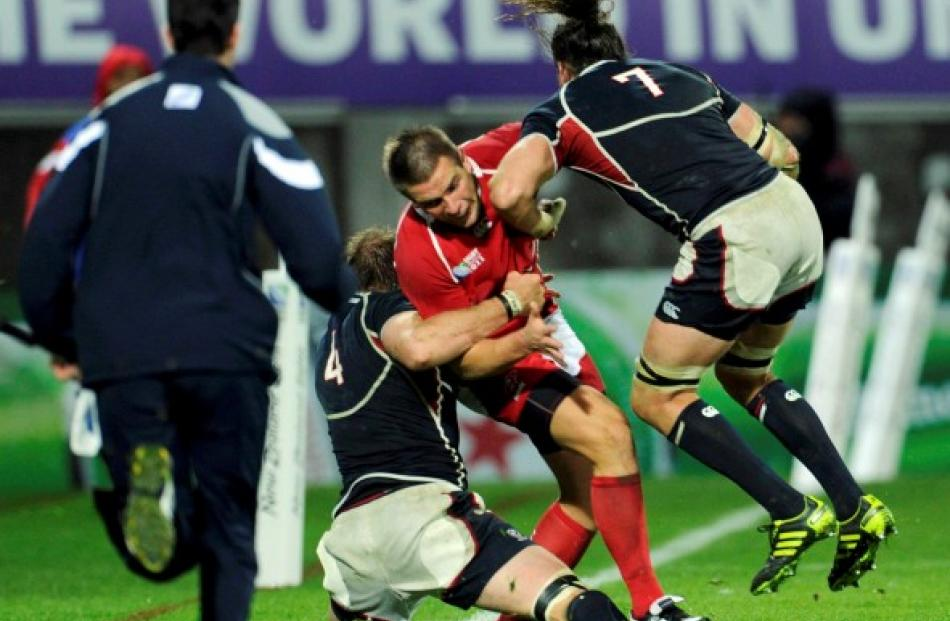 US captain Todd Clever (R) makes a late charge on Russia's Victor Gresev during their Rugby World...