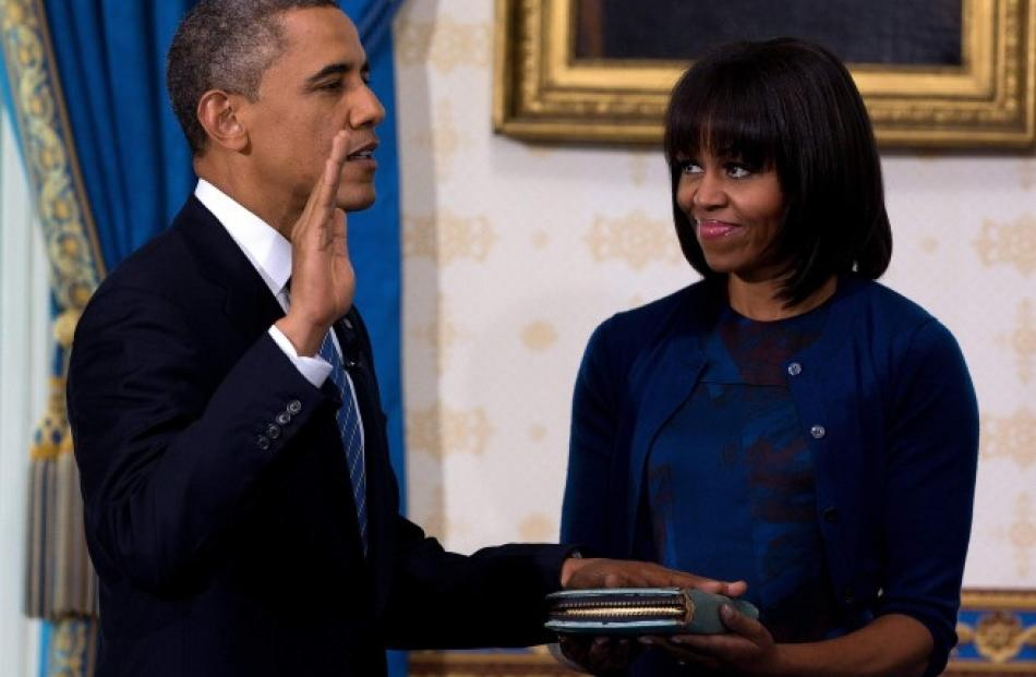 US President Barack Obama takes the oath of office as first lady Michelle Obama holds a bible...