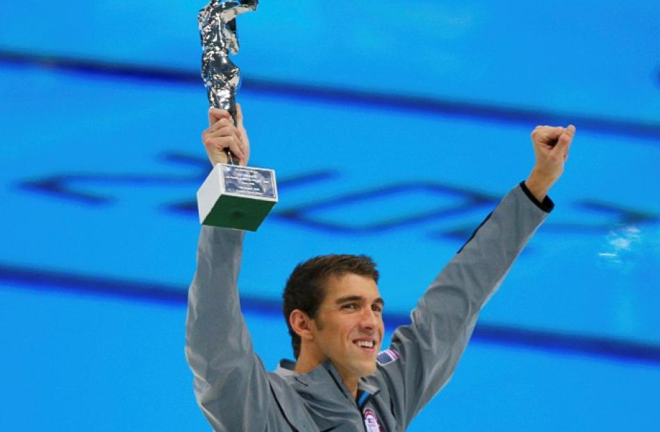 US swimmer Michael Phelps holds up his award recognising him as the most decorated Olympian at...
