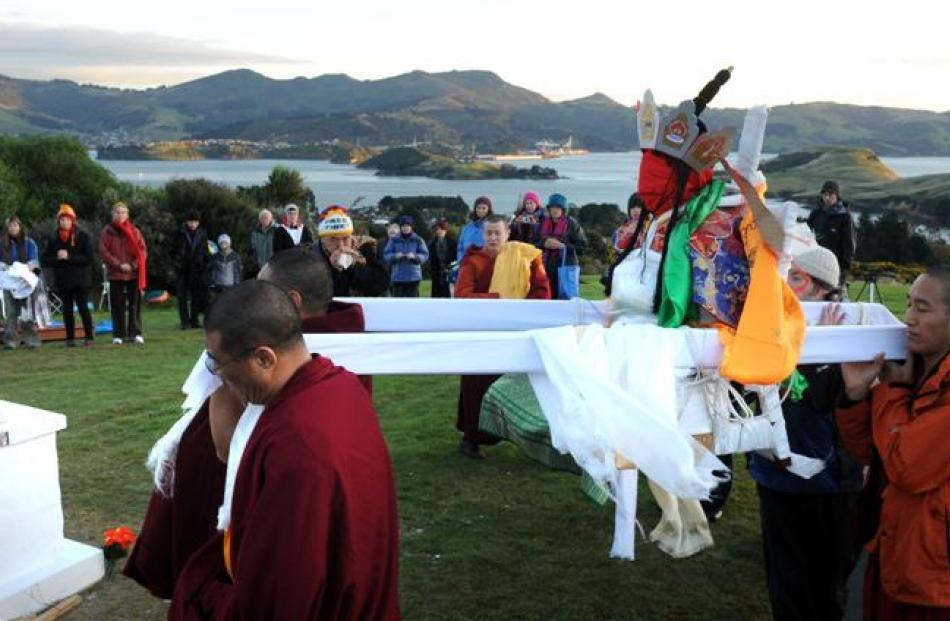 Venerable Jampa Thupten Tulku Rinpoche is carried to the cremation stupa yesterday.