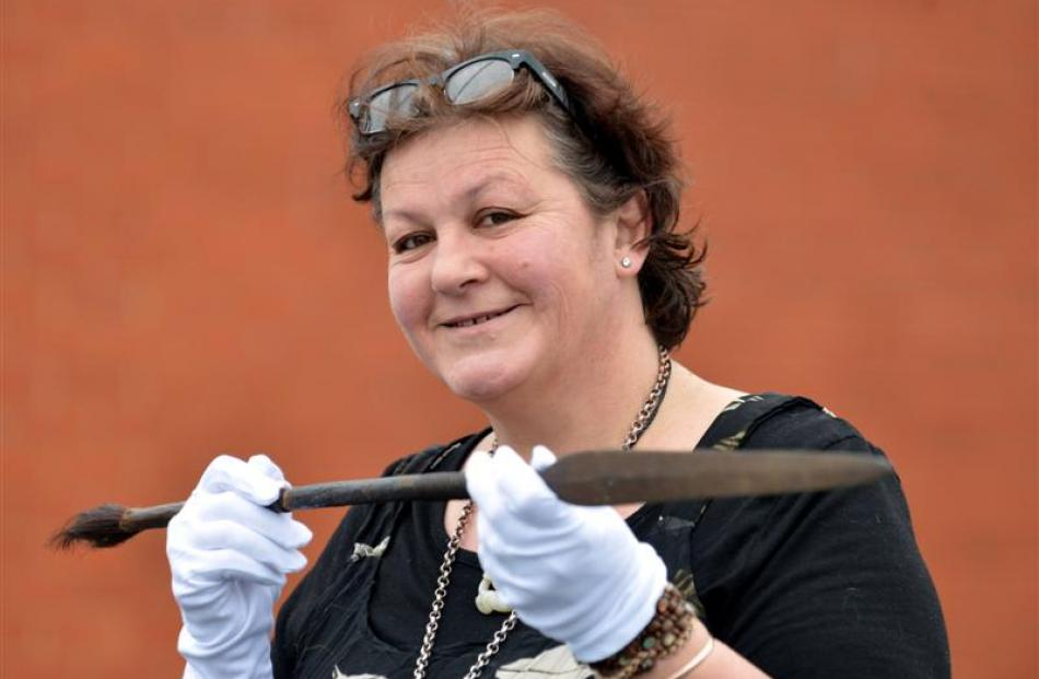 Visiting museum consultant Bridget Wellwood examines a spear, believed to be a relic of the 19th...