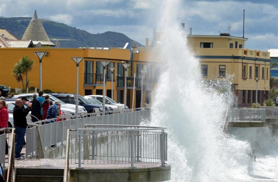 Visitors photograph waves pounding the Esplanade sea wall at St Clair yesterday. Photo by Stephen...