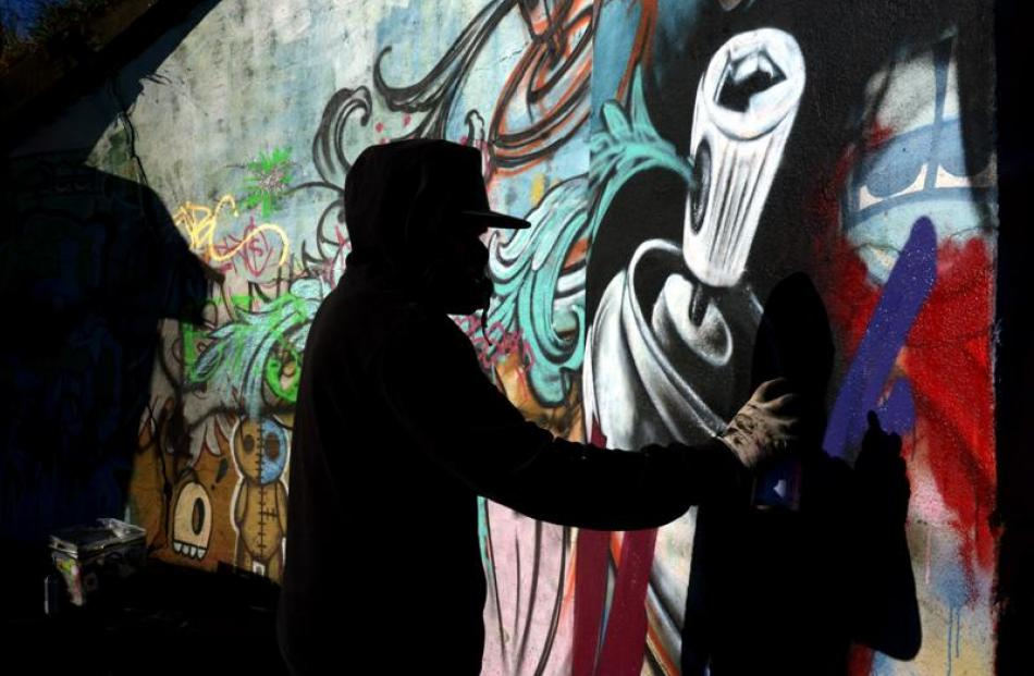 Visual Intelligence tattoo artist Aaron Manuel works on his section of the Community Youth Mural...