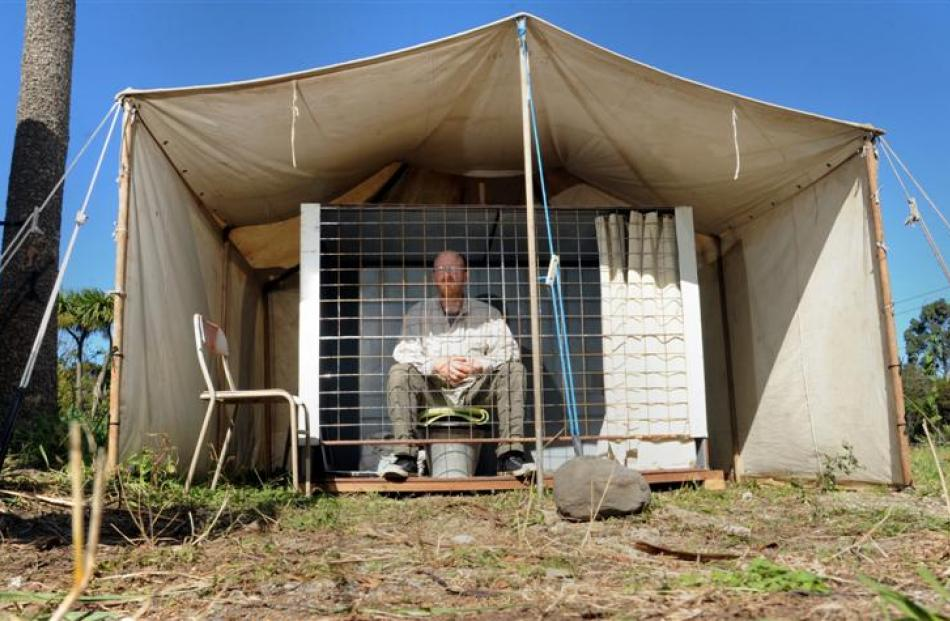 Waitati man Carl Scott in the cage  he  plans to stay in for a month to highlight the plight of...