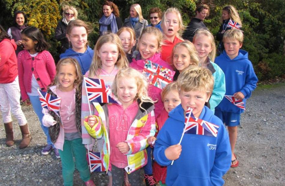 Wakatipu children wave their Union Jacks as they wait for the Duke and Duchess of Cambridge to...