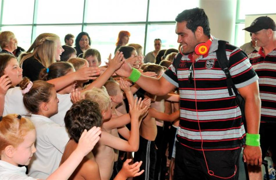 Warriors player Konrad Hurrell high-fives with children from the Fairfield School kapa haka group...