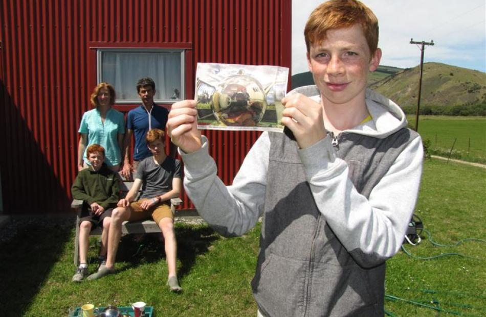 William Lorimer (14) displays his winning photo while mum Michelle, dad Mike and brothers Tom (10...