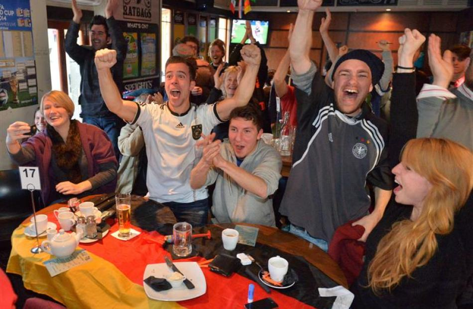With their country's flag serving as a tablecloth, German supporters (from left) Sahlia Kumst,...