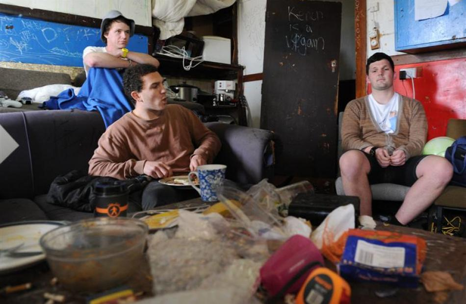 WORST FLAT: Sam Coombs (21), Josh Packer (20) and Jamie Lockyer (19) sit among the filth in the...