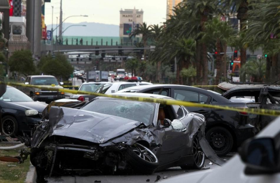 Wrecked cars are seen on Las Vegas Boulevard and Flamingo Avenue as police investigate a shooting...