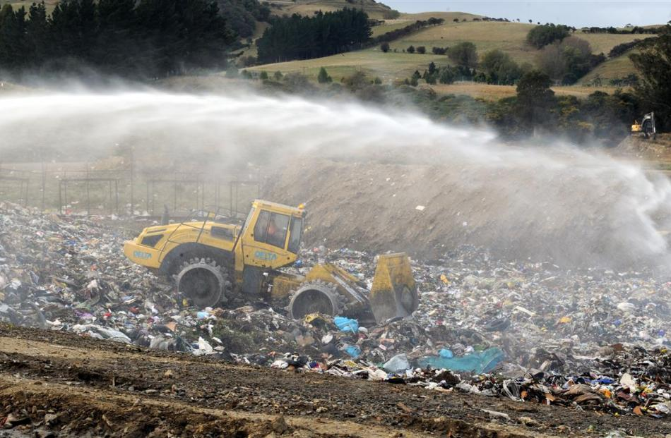 A digger  exposes hotspots for firefighters at  the Green Island landfill yesterday, after a fire...