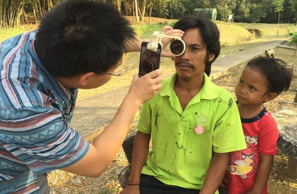 Dr Hong Sheng Chiong checks a patient for eye illness in Borneo. Photo supplied.