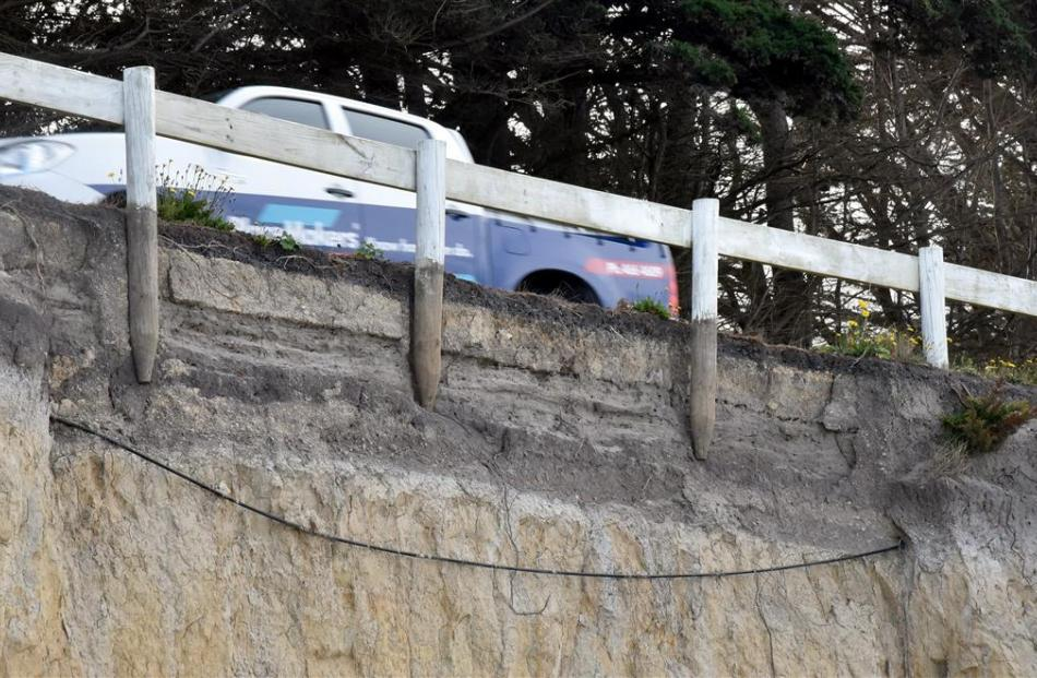 Erosion along Taieri Mouth Rd has exposed three fence posts, a telecommunications cable and the...