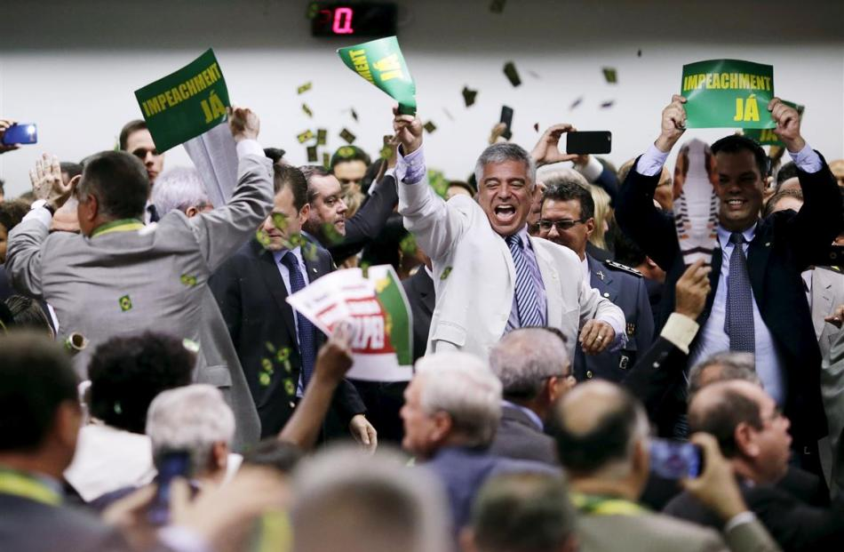 Members of the impeachment committee celebrate after voting on the impeachment of Brazilian...