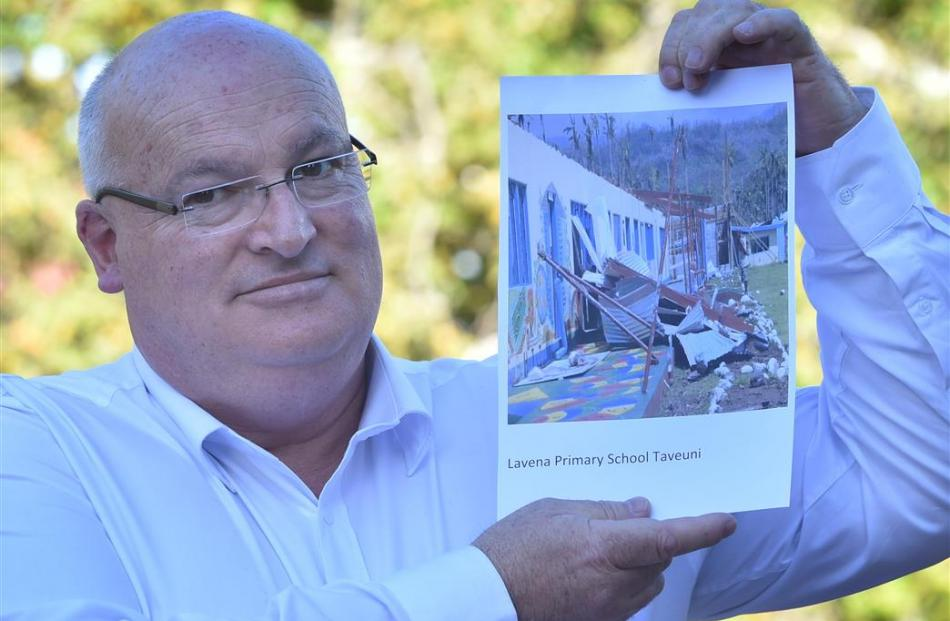 Mosgiel Rotarian Lindsay Thorburn with a photograph of a school in Fiji destroyed by Cyclone...