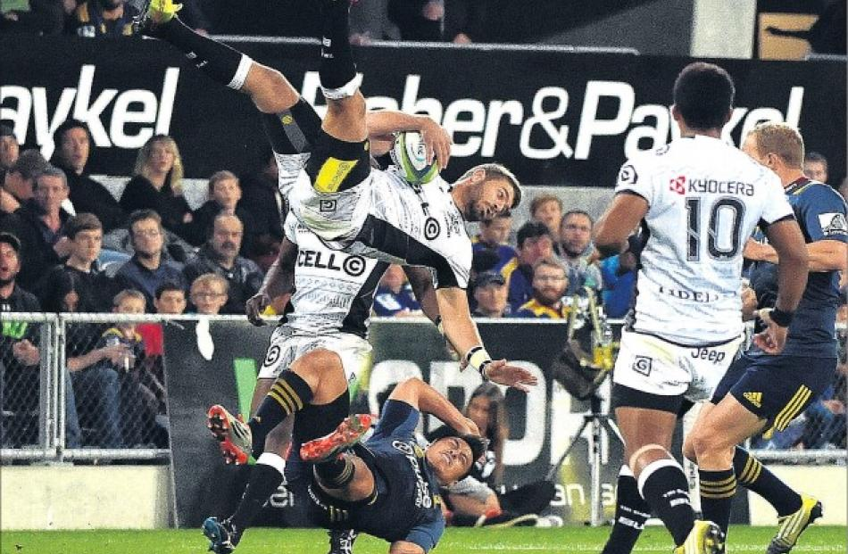 Sharks fullback Willie Le Roux is airborne after the collision with Highlanders second five...