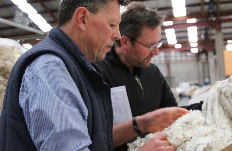 Andrew Raeber (left), of New England Wool, is assisted by Guy Spooner during judging of the Otago...
