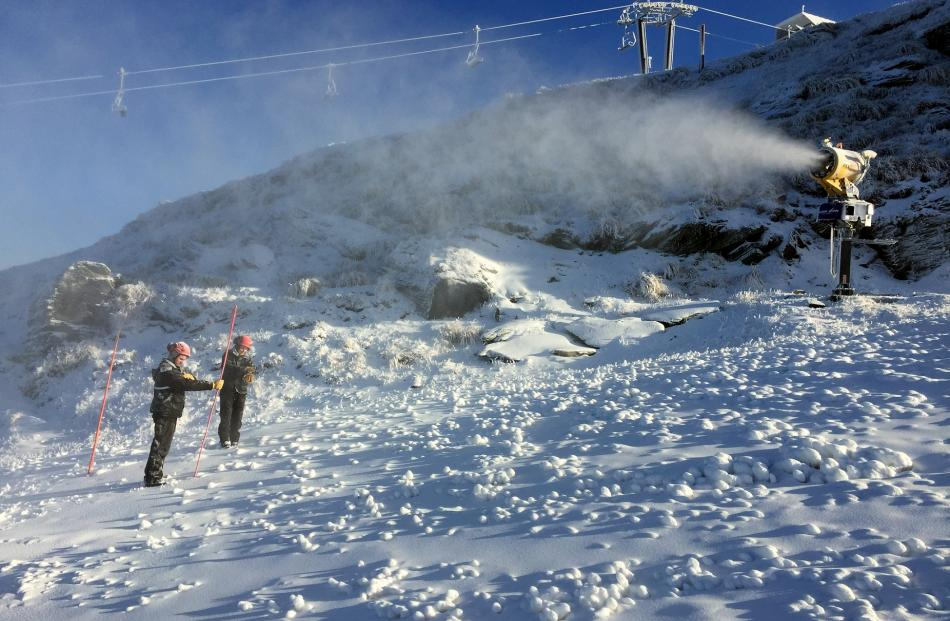 Coronet Peak snow-making team members Jake Reilly (left) and Lucy Ruck measure the snow on the...