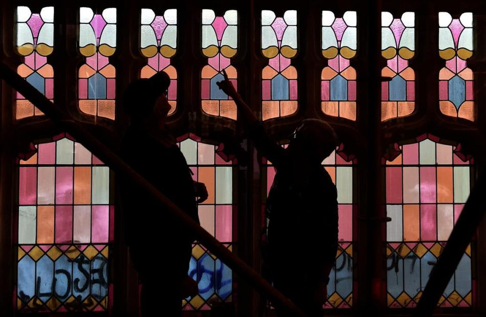 Hanover Hall owners Lloyd Williams and Cally McWha inspect a stained glass window in the former...