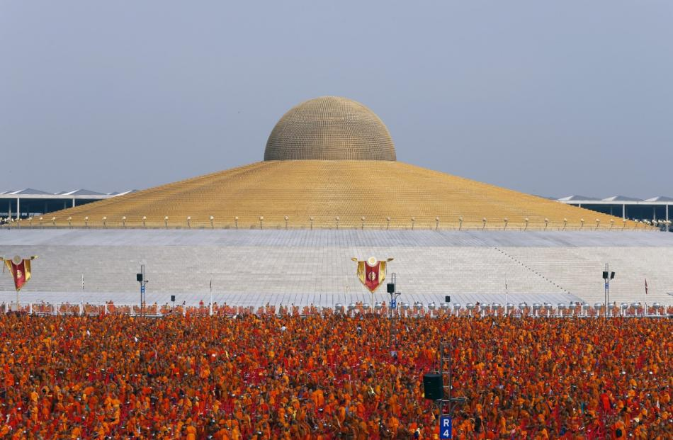 Buddhist monks and novices gather to receive alms at Wat Phra Dhammakaya temple in Pathum Thani,...