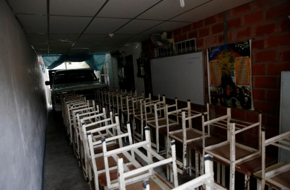 Desks are seen at an improvised classroom in a garage of a house, which is part of state school...