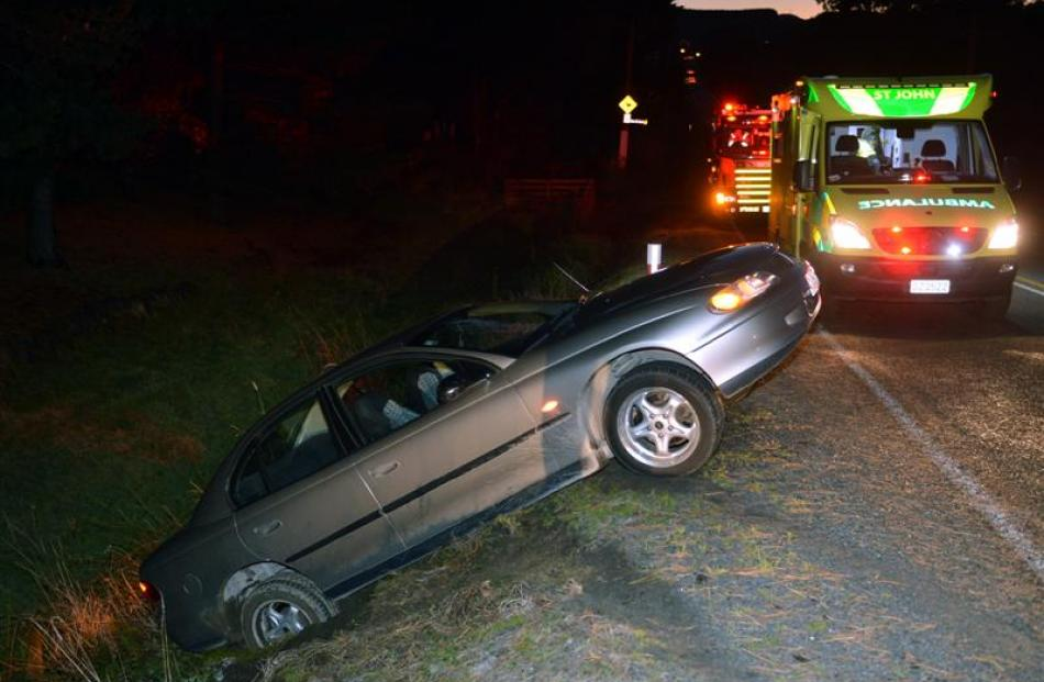 A car sits partly in a ditch after leaving Brighton Rd yesterday. Photo by Stephen Jaquiery.