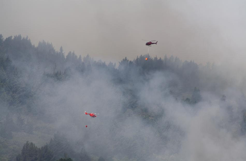 Two helicopters with monsoon buckets battle the blaze on Signal Hill. Photo: Charlotte Steel