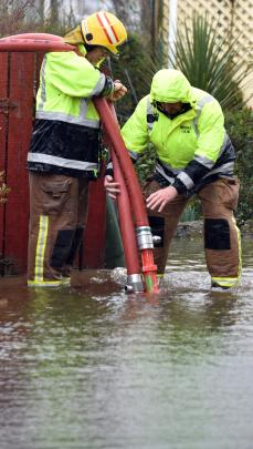 Firefighters work to pump water from a flooded street. Photo: Peter McIntosh