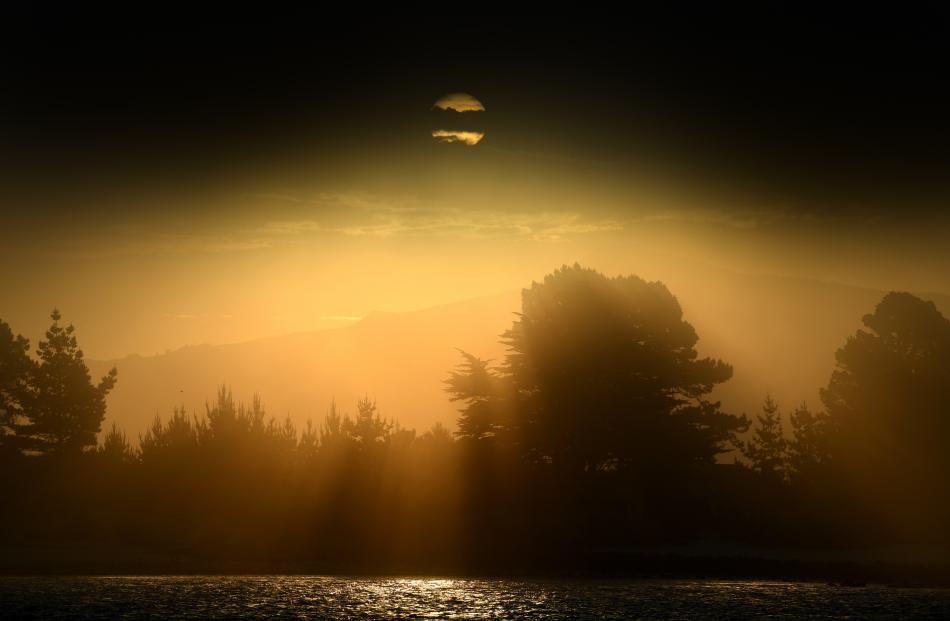 A cloud runs through the sun over the Aramoana spit on Monday night. Photo: Stephen Jaquiery