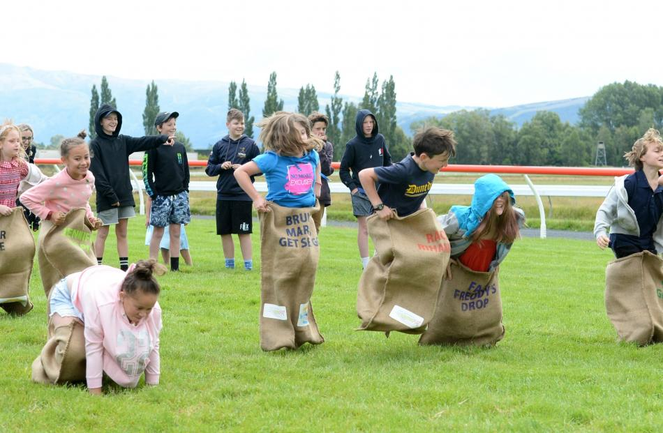 Children compete in a sack race at The Interislander Summer Festival at Wingatui Racecourse on...