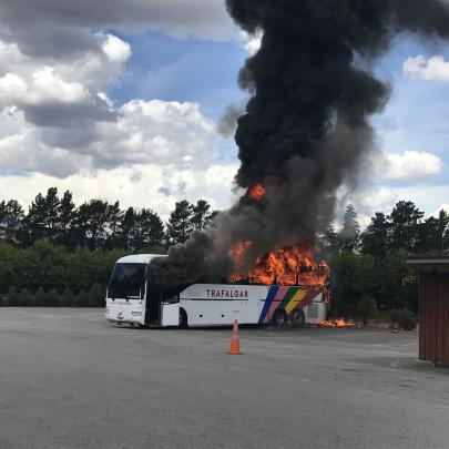 A tourist bus is engulfed in flames outside the Jones Family Fruit Stall in Cromwell yesterday. Photo: Richard Jarosch