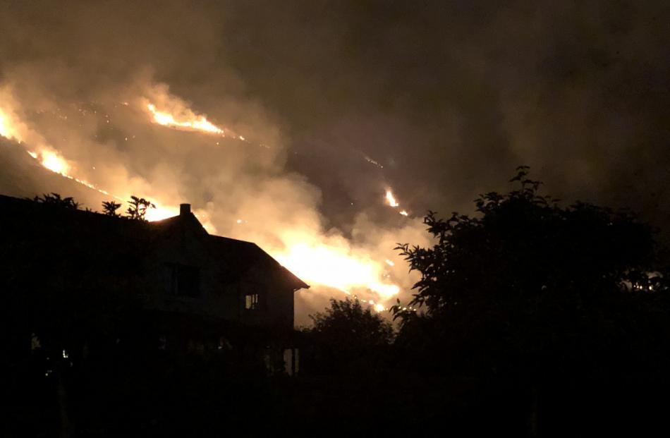 Flames burn near a house in Wanaka last night. Photo: Cameron Romeril