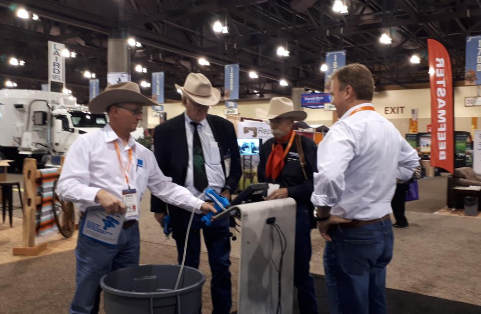 Te Pari Products' United States representative Brian Siekman (left), brand ambassador Baxter Black (third from left) and sales and marketing director Jeremy Blampied (right) discuss drenching options with a customer at the National Cattlemen's Beef Associ