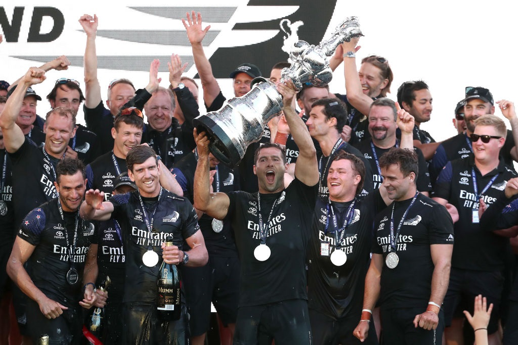 """Emirates Team NZ celebrate with the """"Auld Mug"""" trophy after successfully defending the America's..."""