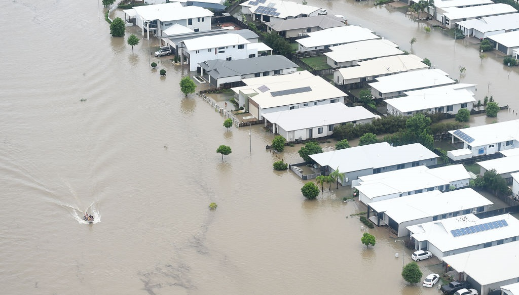 A boat motors along a flooded road in Townsville. Photo: Getty Images
