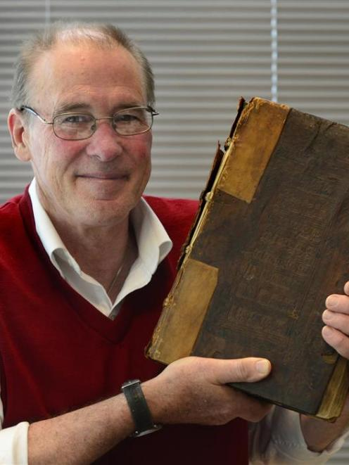 University of Otago special collections librarian  Donald Kerr holds up the 15th-century book...