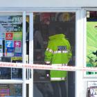 Police inside the Highgate Dairy yesterday. A masked man attempted to rob it at knife-point on ...